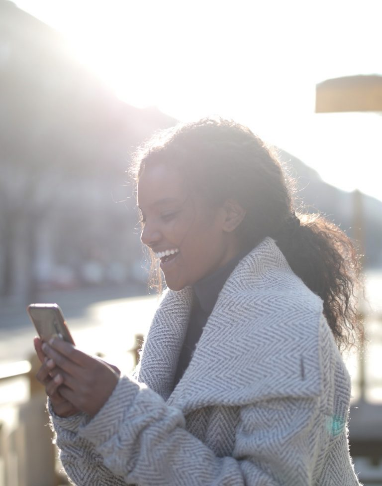 Female holding a smart phone and smiling
