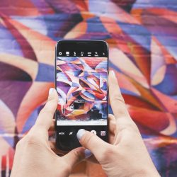 Hands holding a phone up in front of street art - abstract shapes in red, orange and purple