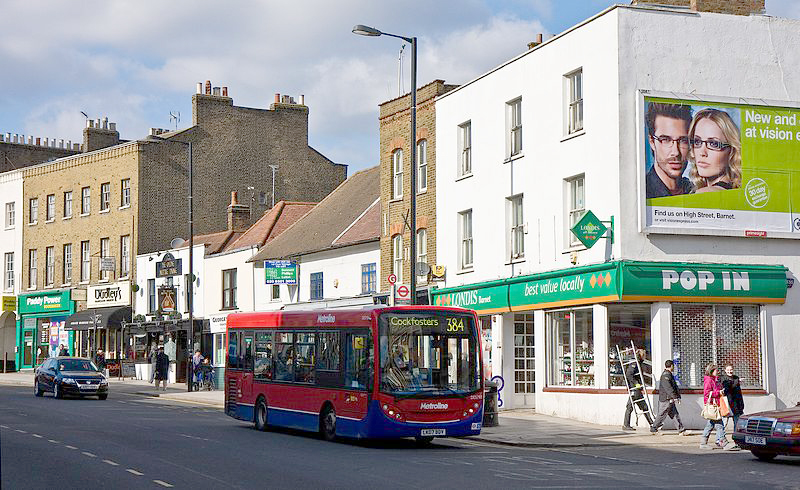 London high street of shops, with a red and blue single-deck bus in the foreground