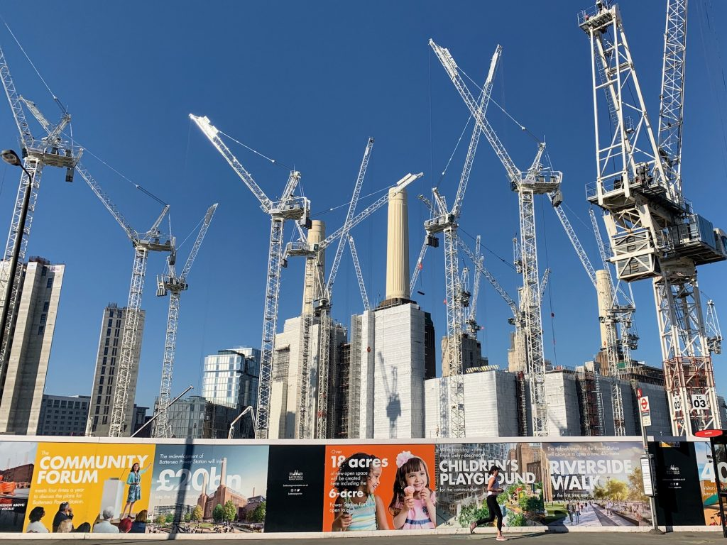 Cranes against a bright blue sky during construction of Battersea Power Station. Multi-coloured signage is shown in the foreground.