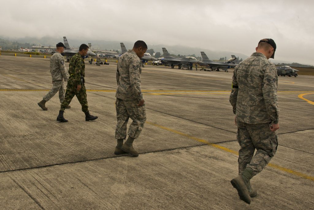 U.S airmen walk across a military airfield looking for foreign object debris