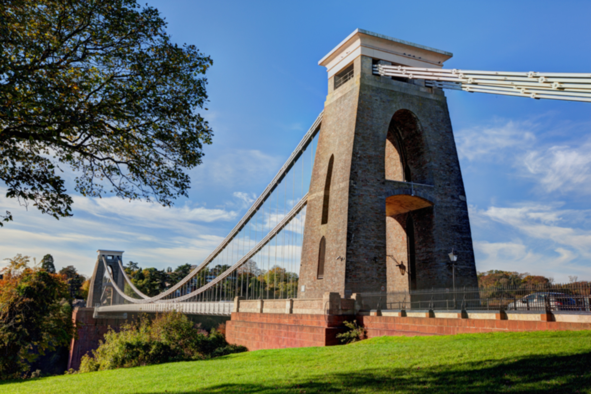 Shot of the Clifton Suspension Bridge, taken from the Clifton side and looking across the bridge to the other side. It's a bright sunny day with blue sky and a few clouds