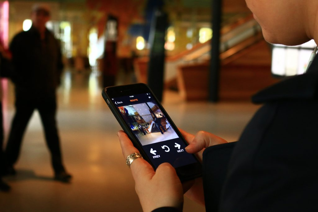 A woman's hands holding a smartphone, with the UCAN Go app open on it. The background shows people within the Wales Millennium Centre.