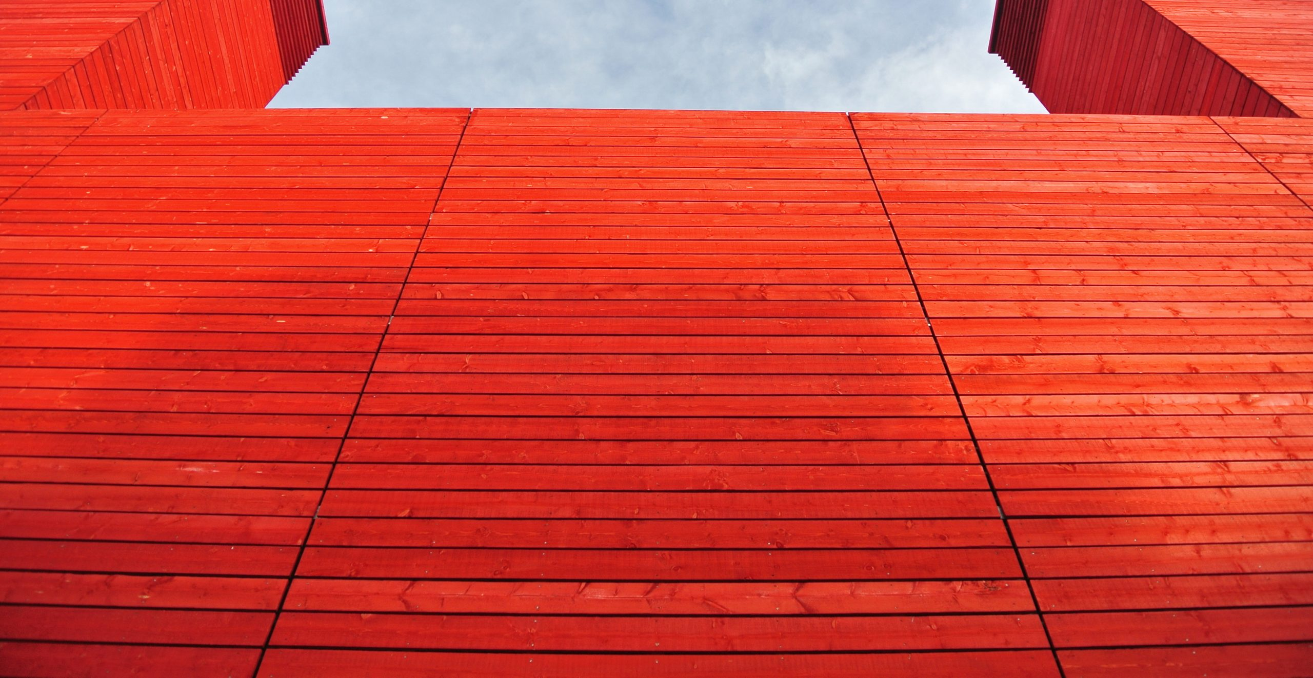 Shot from a low angle, this image shows the eye catching outside of the National Theatre - red panels across the building