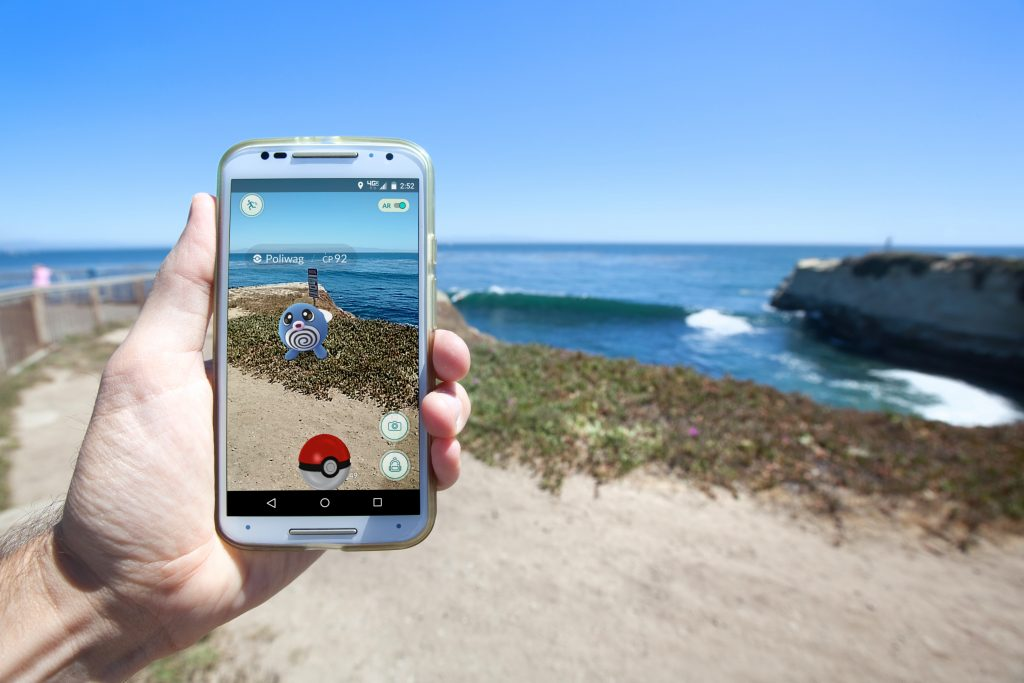 Photo of a man's hand holding an Android phone, with Pokemon Go displayed (a polywag and pokeball are on screen with A.R. enabled), the phone is held up towards the sea, with sand, seaweed and rocks.