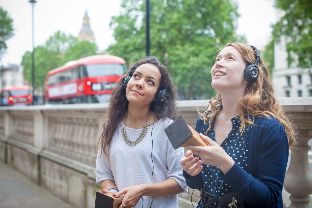 Two women look upwards whilst smiling, wearing headphones and holding the Lost Palaces wooden devices in their hands. A red London double-decker bus is passing in the background, along a tree-lined street.
