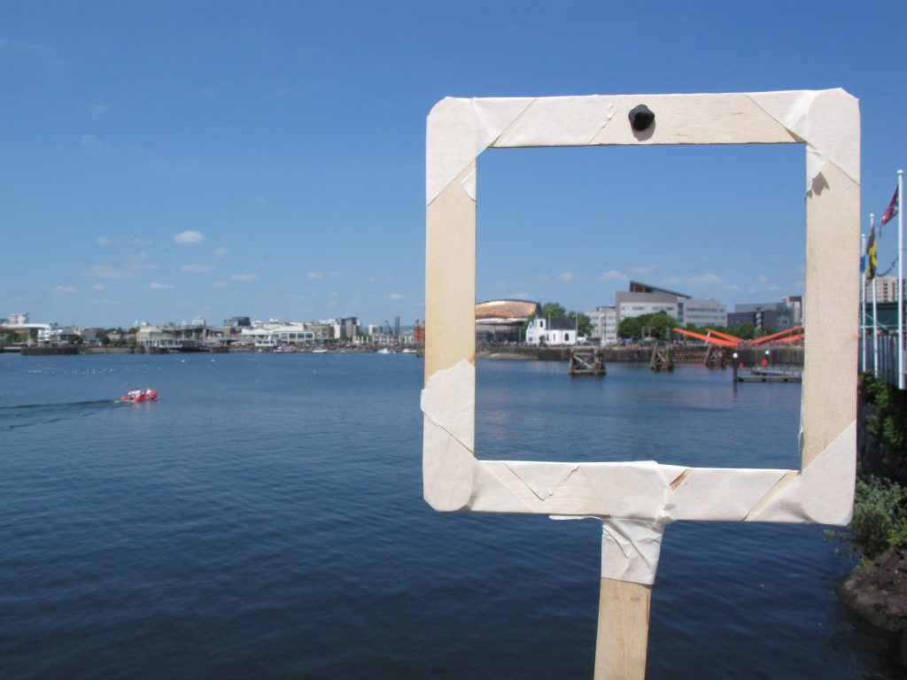 Cardiff Bay is shown across the water on a sunny day, whilst a viewing window made of lollipop sticks and masking tape is being held up to frame several buildings in the distance.