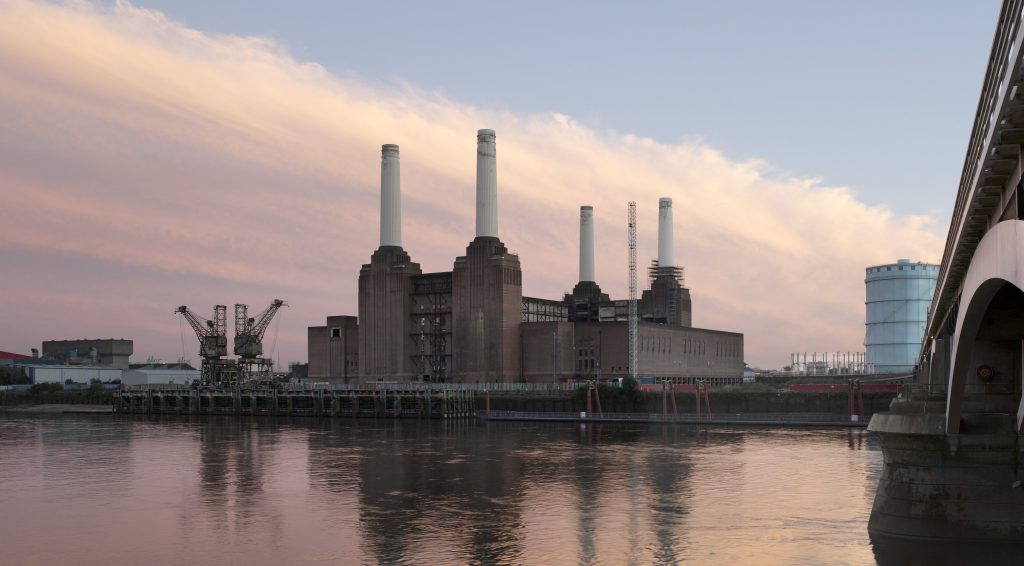 Battersea Power Station is shown from across the River Thames at dusk. The building's four white chimneys stand out against the pink sky, and the building is reflected dully in the river's surface.