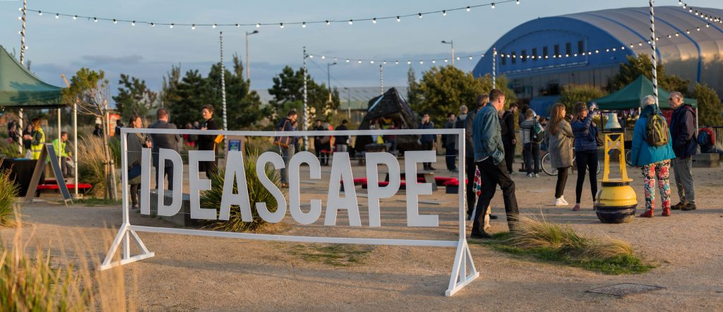 "A white sign reading ""Ideascape"" stands in-front of the Porth Teigr event. In the background, people are moving or gathering around the exhibits, in the dusk light."