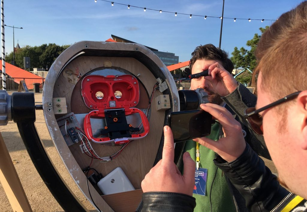 A man with a screwdriver is working on the AR Binoculars demo. The binocular casing is open, to reveal a wooden shell housing red AR devices inside.
