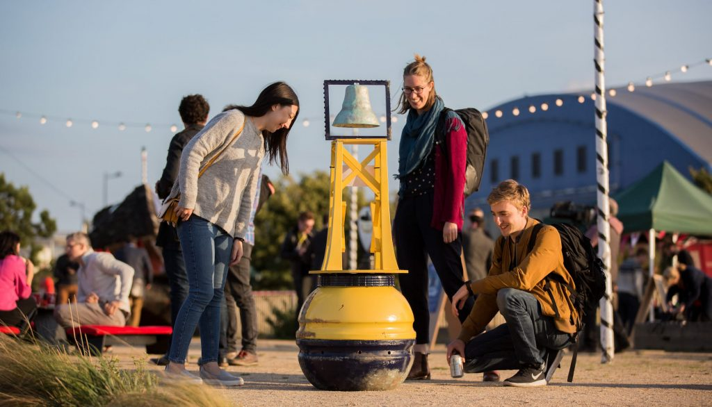 "Three people looking at the ""Digital Town Crier"" demonstration, which is modelled like a bright yellow buoy, topped by a copper bell."