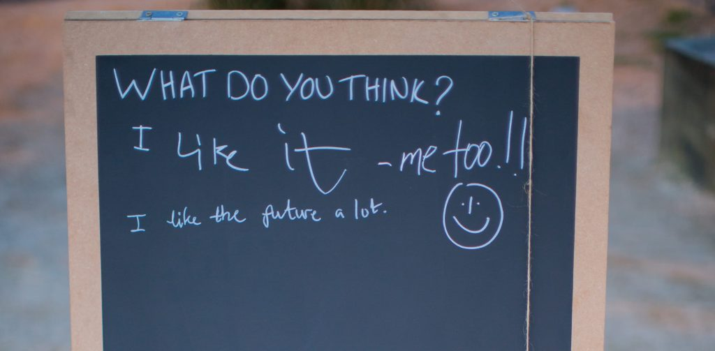 "An A-board outside, with a chalkboard panel - containing the question ""What do you think?"" written on it. Someone else has written, ""I like the future a lot"" alongside a smiley face."