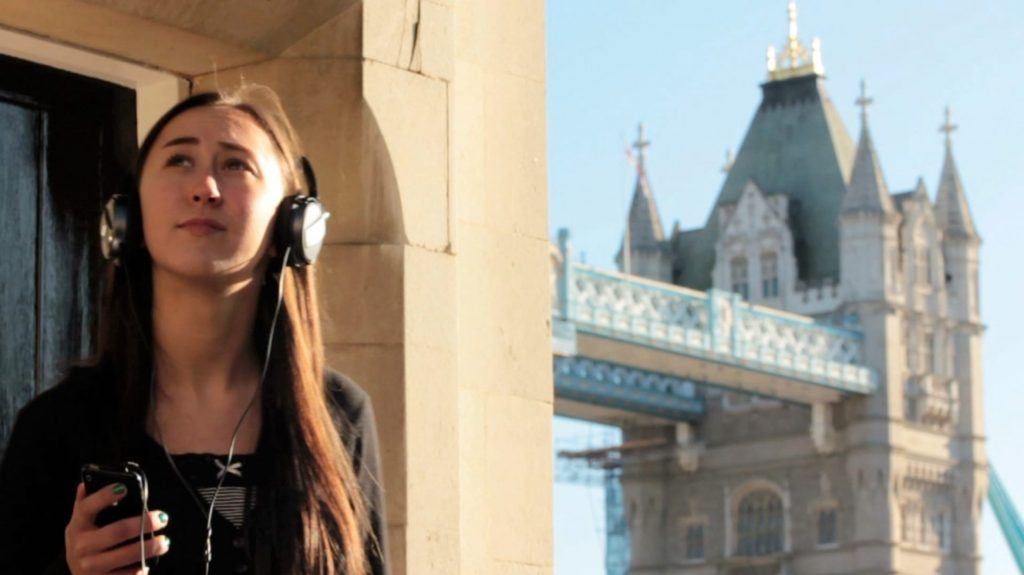 A woman wearing headphones and holding a smartphone is looking up, Tower Bridge is seen in the background, with the yellow stone walls of the Tower of London.