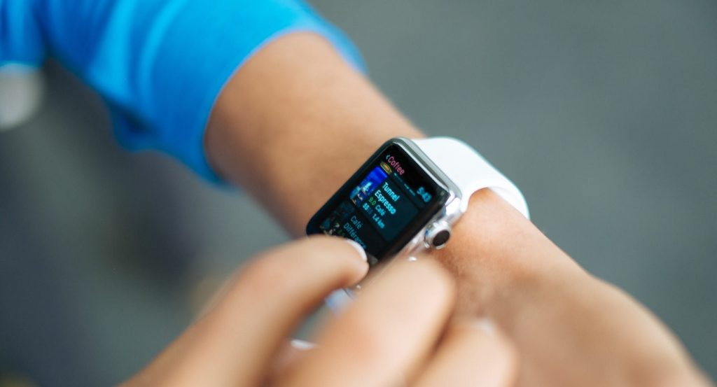 Photo of a women's arm wearing an Apple Watch and an azure blue jumper.