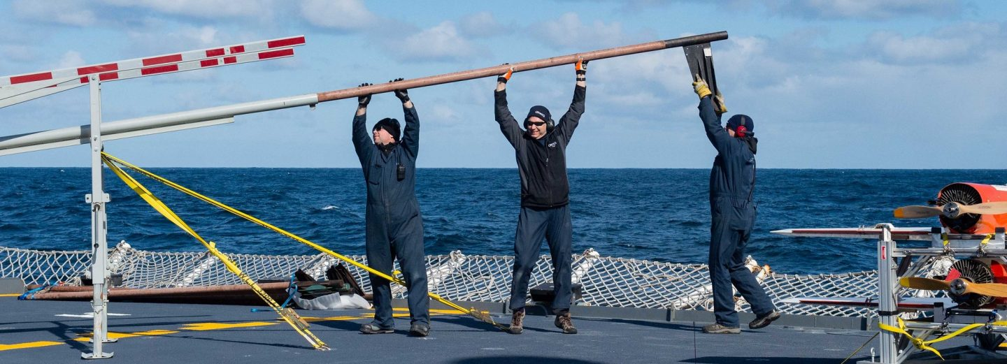 3 men wearing QinetiQ uniforms work on the deck of a naval ship, holding a pole horizontally as if trying to line it up to fit into a structure