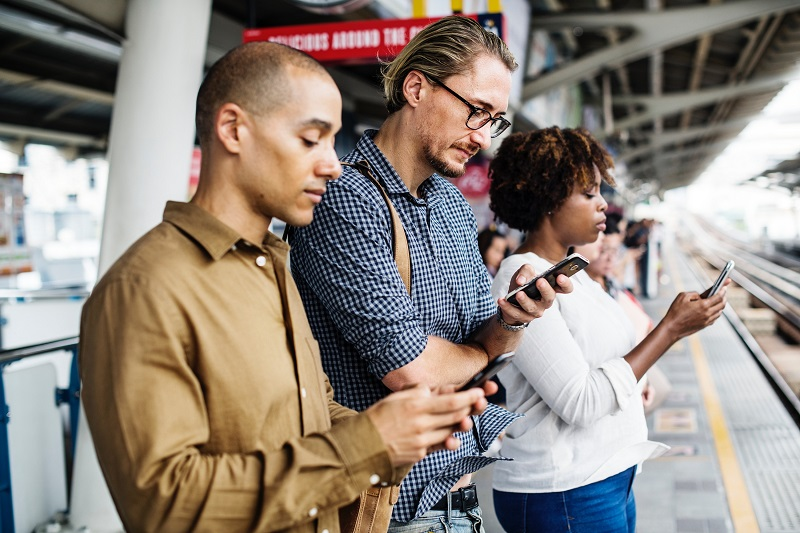 Three people look at smart phones at a train station