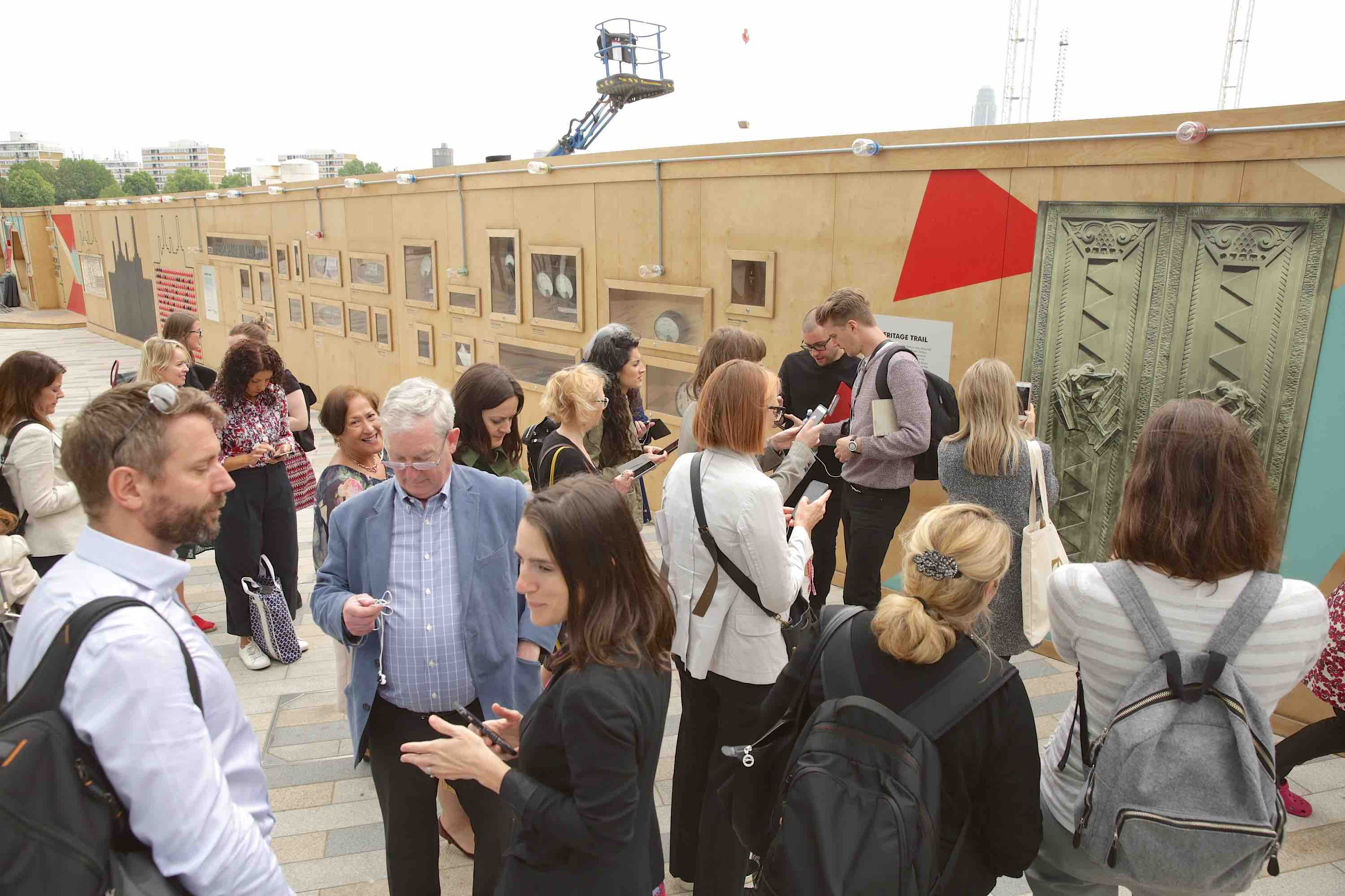A crowd of people gather outside, in front of a wooden wall to try the AR Door installation at Battersea Power Station