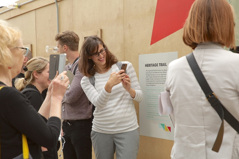 People smile holding smart phones up at the Battersea Power Station heritage wall, with a poster of the Heritage Trail app