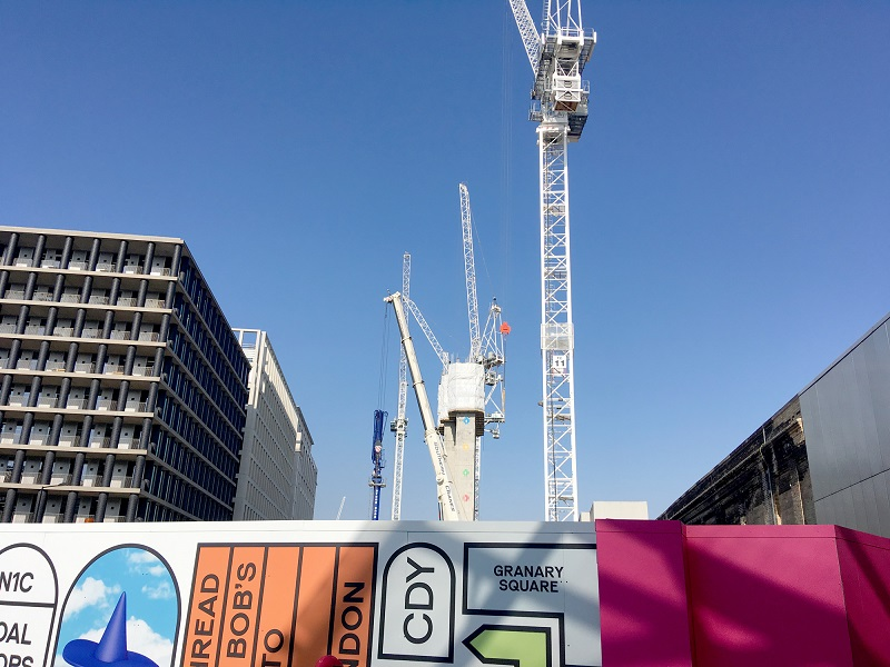 White cranes against a blue sky, with colourful hoarding surrounding a building site below