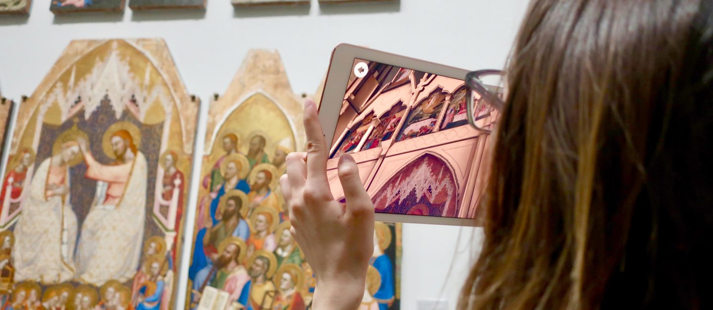 A woman seen from over the shoulder, holding up a tablet to an altarpiece on a white gallery wall