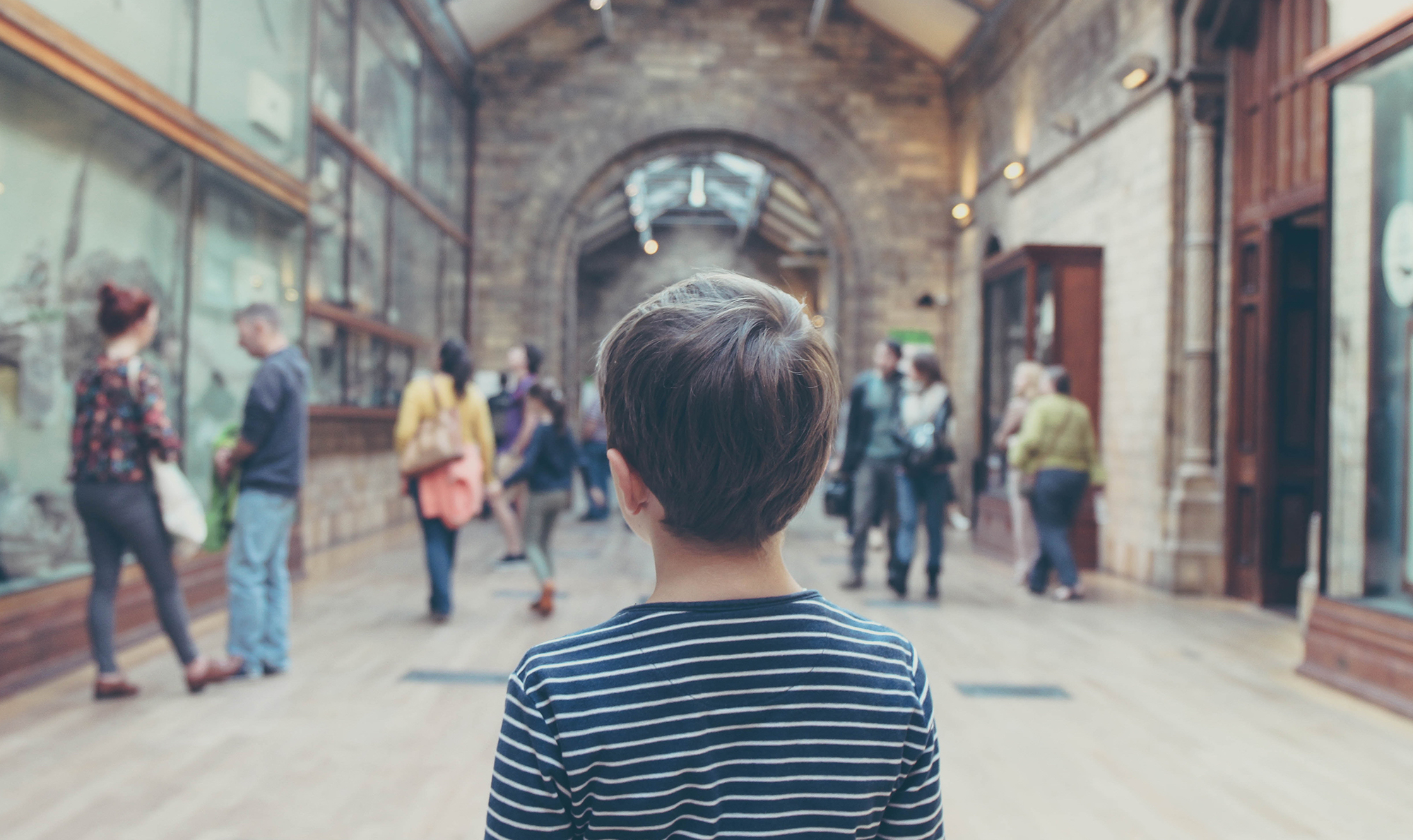 Child looking away from the camera, at a Victorian-style museum hall, with glass cases containing exhibits to the left and adults in the background.