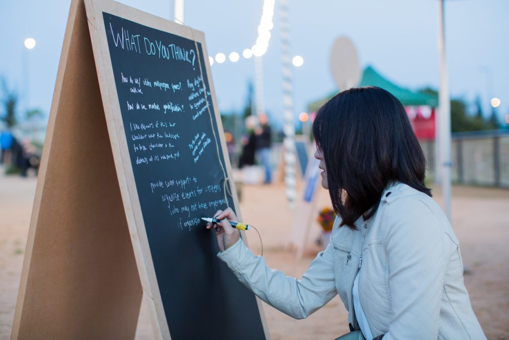 A woman writes on a chalkboard stand outside, in the dusk at Idescape: Porth Teigr, with festoon lights in the background