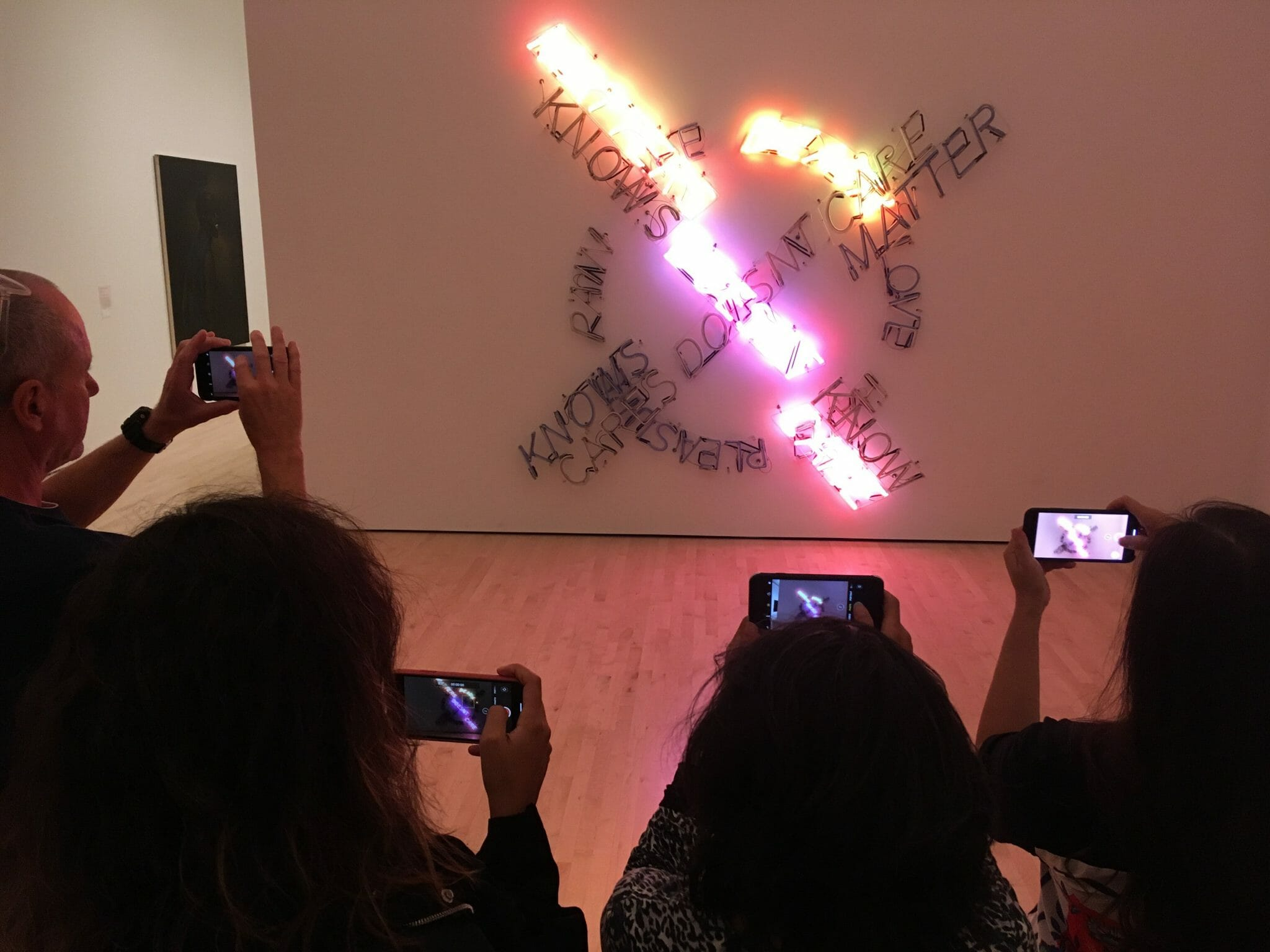 A crowd of people have their phones out to take a photo of a digital interactive exhibit - neon lights in a circle, crossing over with the words 'know' 'care' 'doesn't' - lots of random words