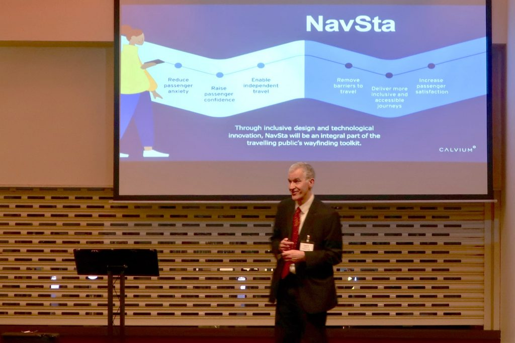 Man stands in front of a projector screen, with an illustration of the NavSta project on it