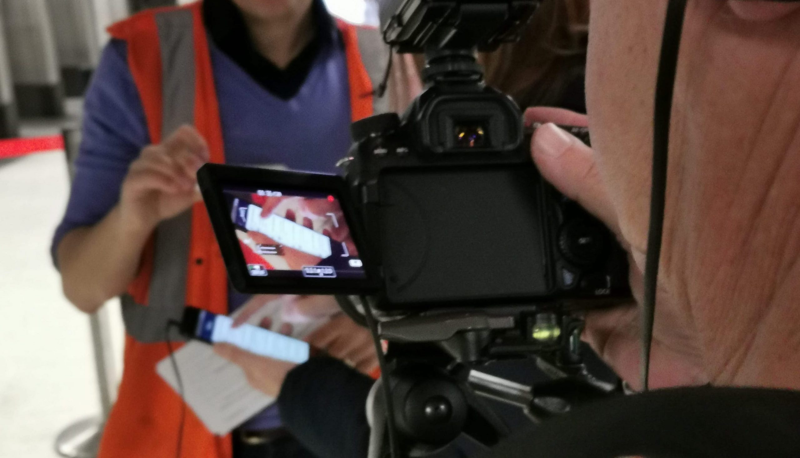View through a digital camera at a person holding a phone. People in orange hi-vis vests in the background.