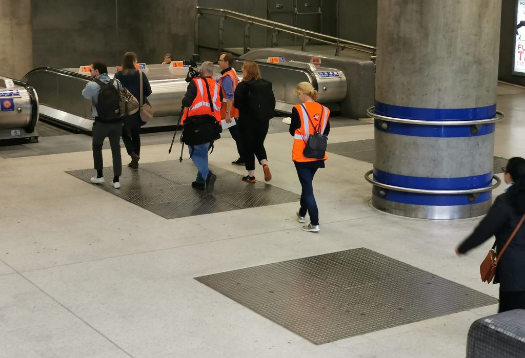People in orange hi-vis jackets walk through a train station, seen from a level above, with their backs to the camera