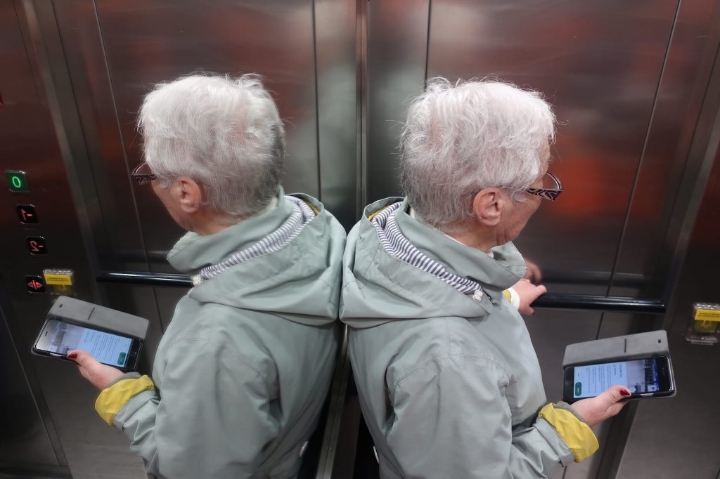 Person with white hair stands in a lift, holding a phone in their hands.