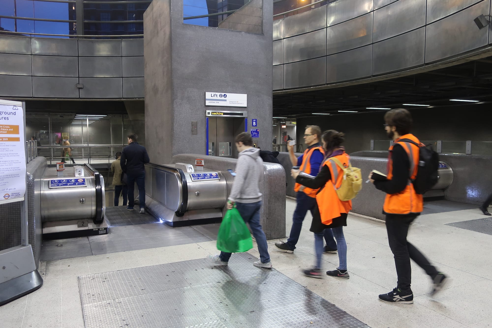 People in a train station. Three people in orange hi-vis jackets are walking behind a person holding a phone.