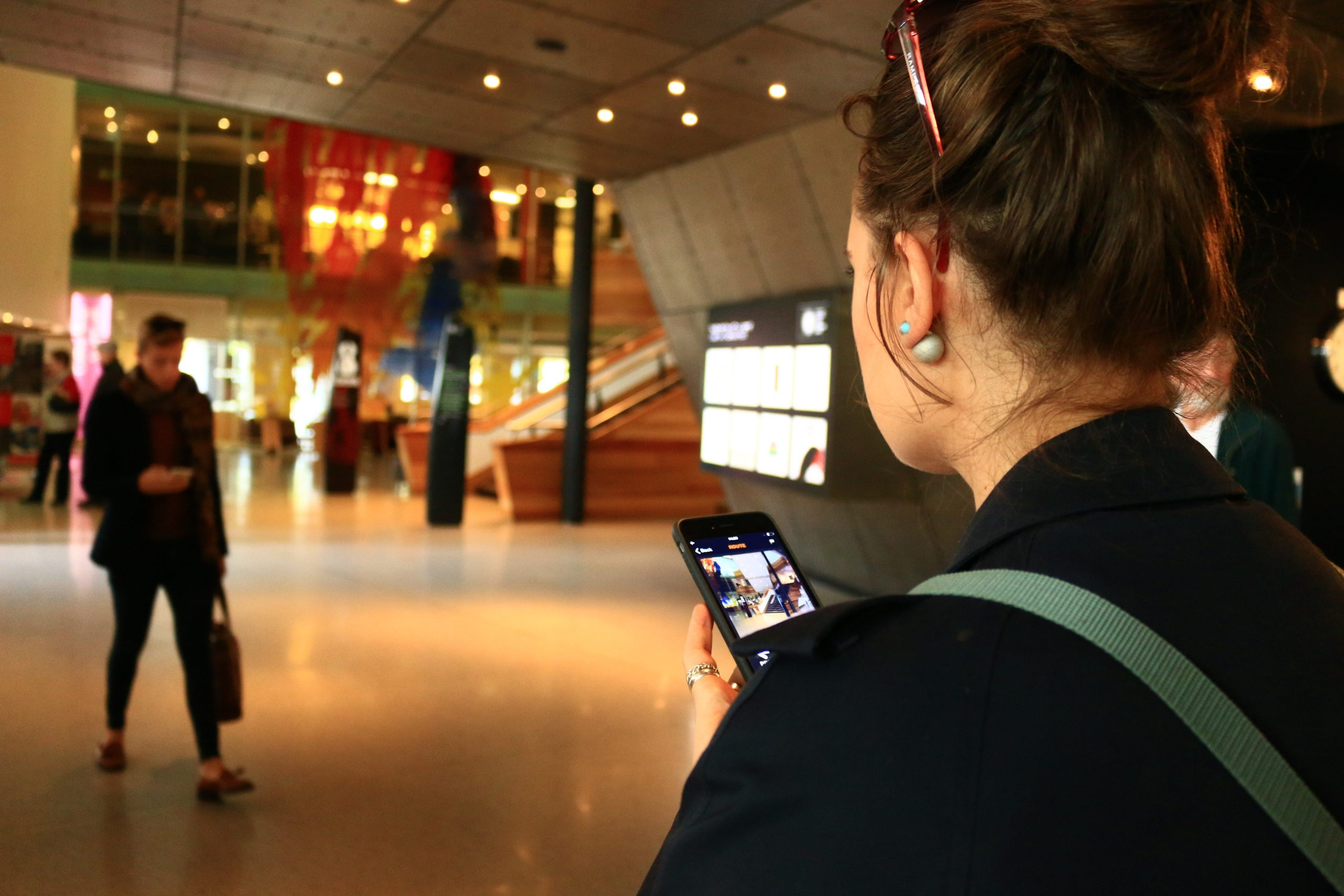 Photo of person in Wales Millennium Centre using UCAN GO on phone