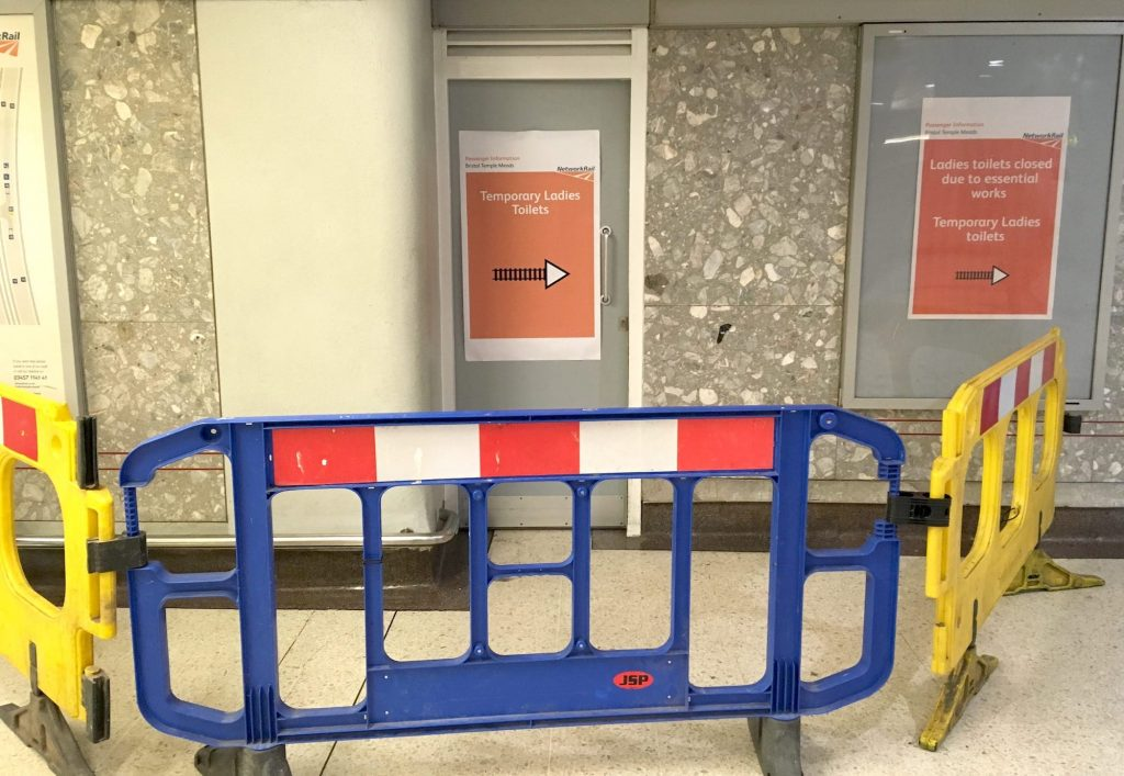 "Train station toilet door with an ""out of use"" sign attached and physical barriers blocking the path."