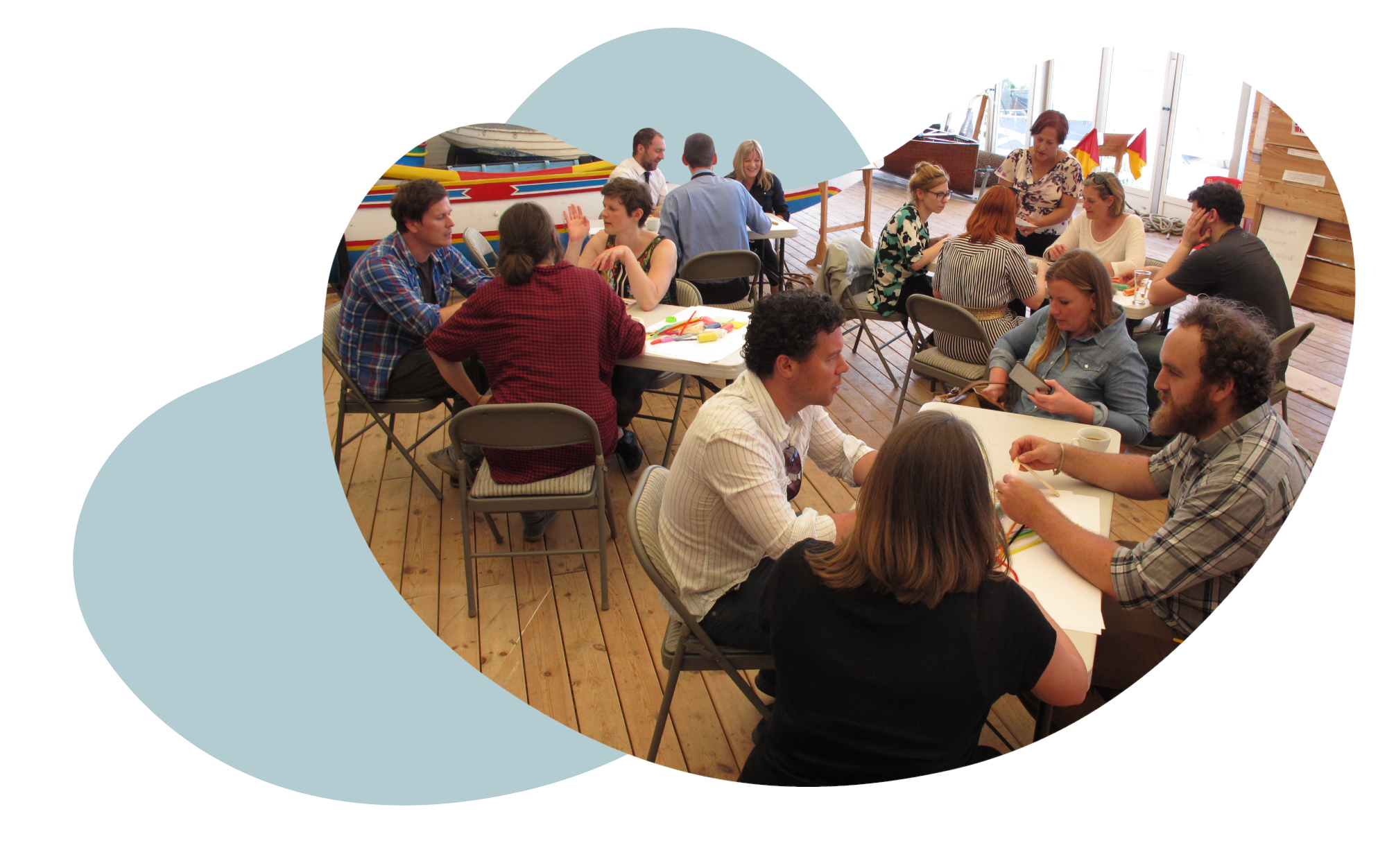 Image shows a group of people sat at different tables in smaller groups, taking part in a creative ideation workshop