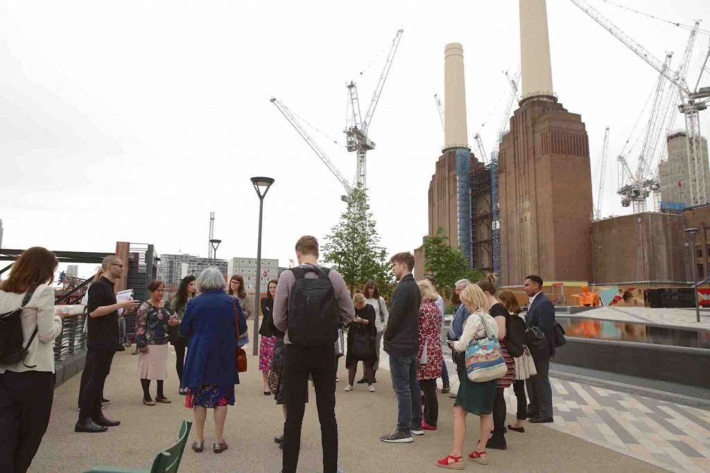 Battersea Power Station is under construction in the background. A group of people gather around the Heritage Trail app team as they are speaking.