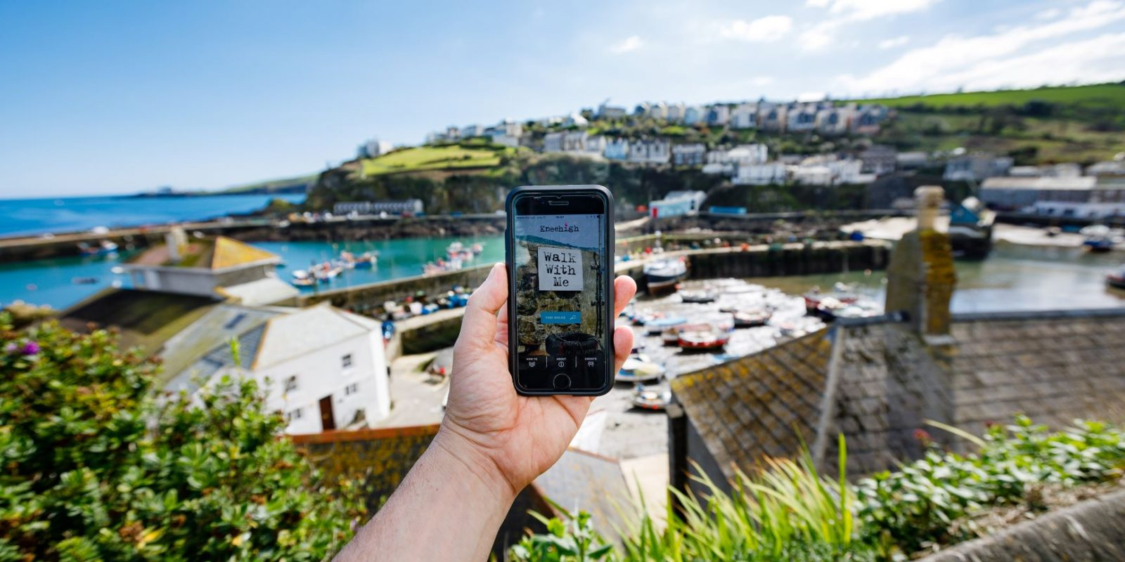 A person holds a phone up against the background of a seaside town's harbour, with blue ocean, houses on the cliffs and an array of fishing boats in the blurred background. In the foreground, the image on the phone is the Kneehigh Theatre Walk with Me app homepage.