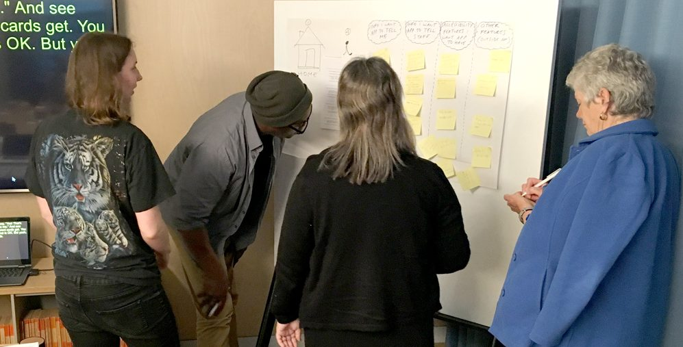 Four people gather around a whiteboard, adding yellow sticky notes as a group