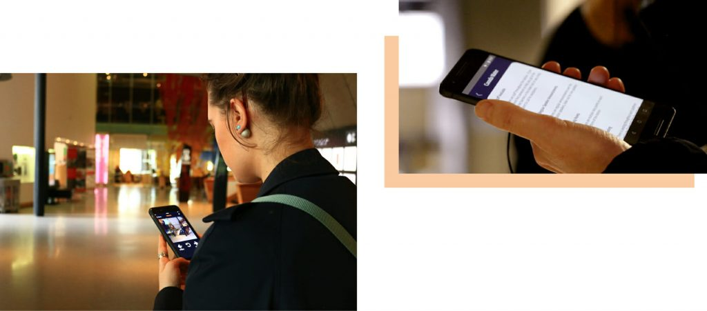 To the left, is an image of a girl holding her phone using the UCANGO app. To the right, someone is holding their phone in their left hand. This is all you can see, and on the phone they are using the NavSta wayfinding app.