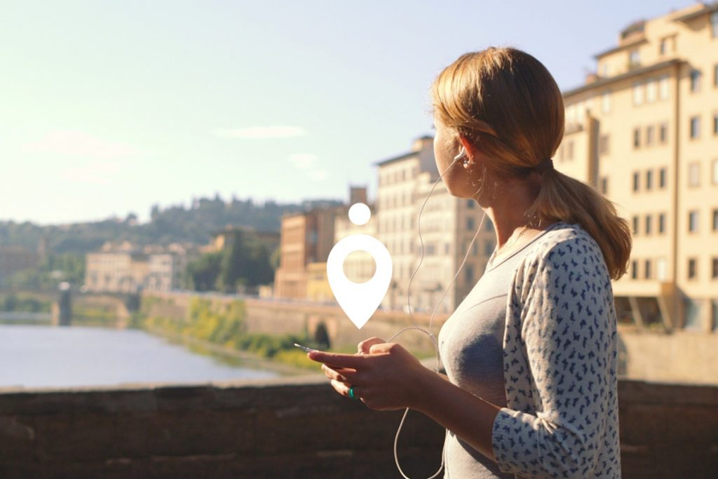 a woman is stood on a bridge in florence, italy and is looking to her right towards the river. She has her phone in her hand with headphones and the place experience platform logo is above the phone, indicating she is using the app.