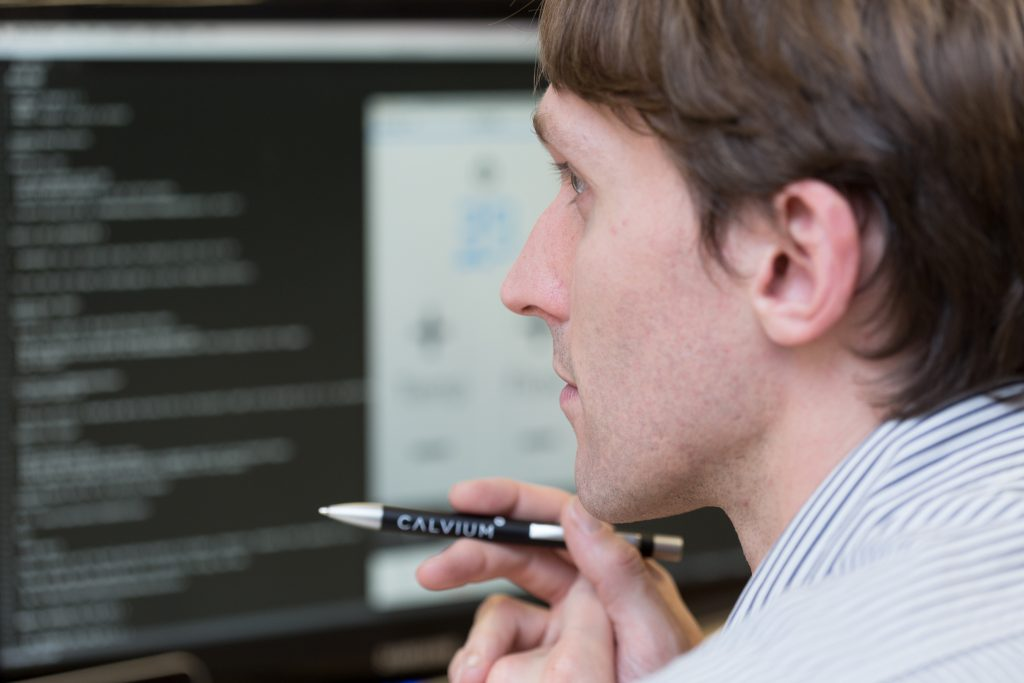 Calvium's technical director, Ben Clayton, is photographed working on some code on a screen. The screen itself is blurred and Ben is holding a pen in thought