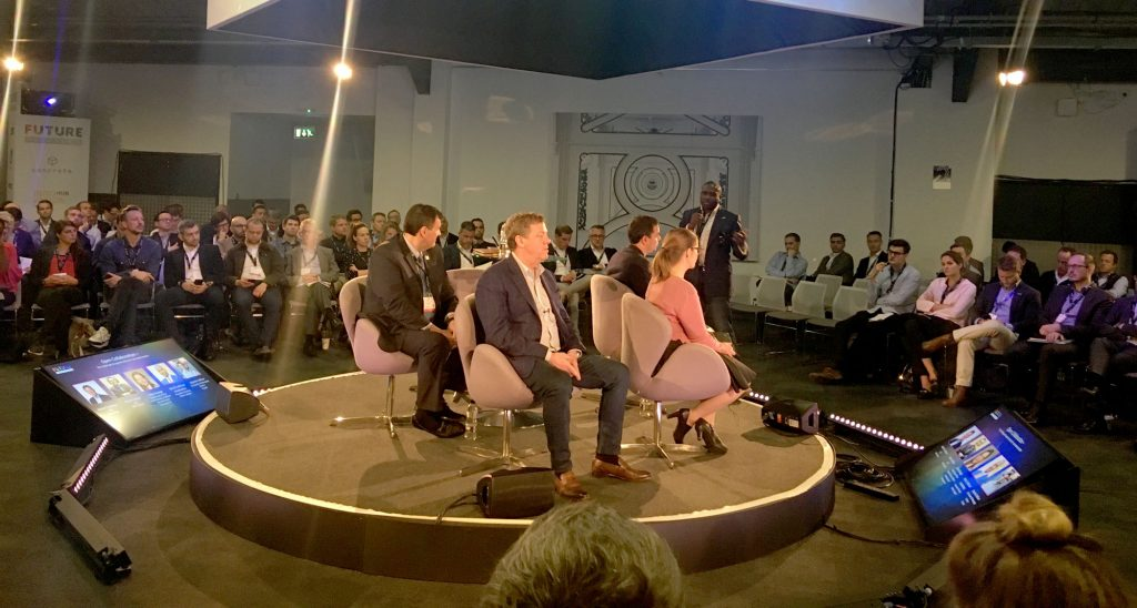 A panel of four people on a circular stage in the centre of the audience - all speakers facing slightly different directions, sat below a projected screen with their profiles