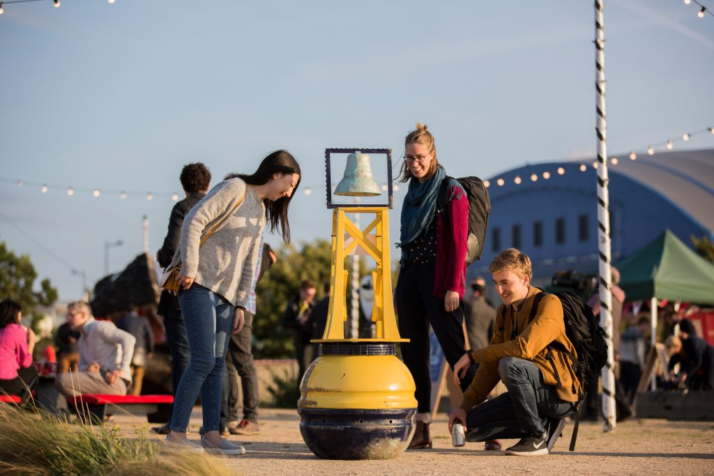 Photo of three people looking at a bright yellow life-buoy on the sand - one of the prototypes for Ideascape: Porth Teigr