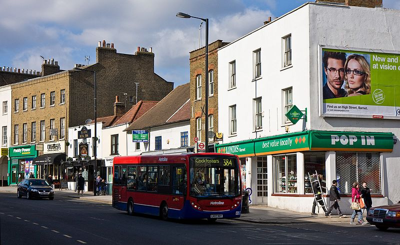 Photo of a high street in London, a single-storey bus going to Cockfosters is at the centre of the shot. Various shops are open behind it, including a Londis, Paddy Power and a pub