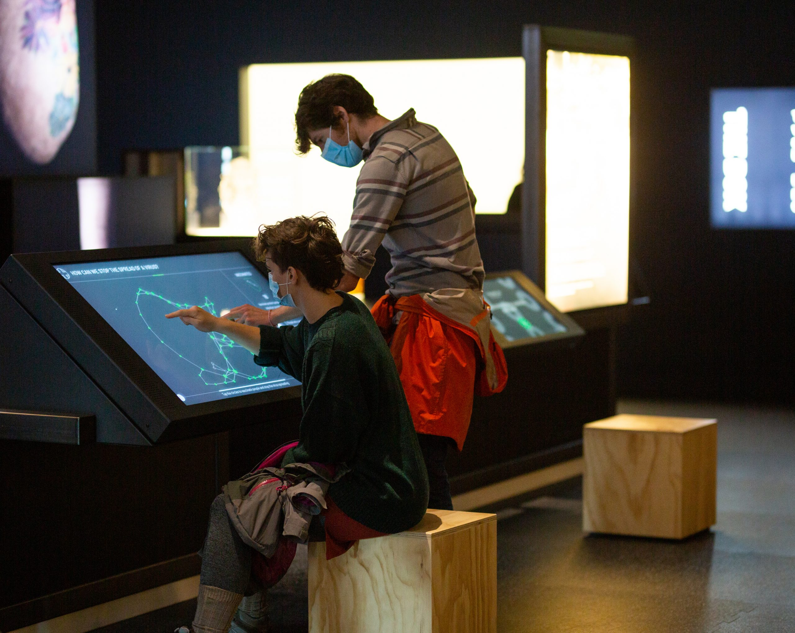 Two visitors to We The Curious are using a large touch screen to map out a constellation and ask a question. They are both male, white, with brown hair and are wearing face masks.
