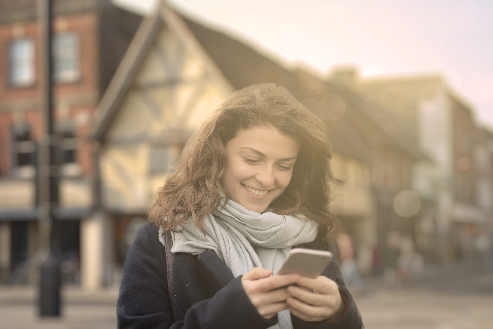 A white woman with long curly brown hair, wears a pale blue scarf and smiles while looking at her phone as she explores Salisbury