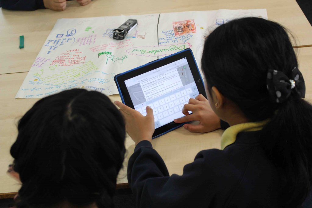 Children with tablet and colourful paper
