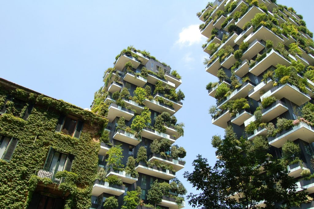 Three contemporary high-rise flats, covered in greenery and trees on every floor, set against a bright blue skyline.