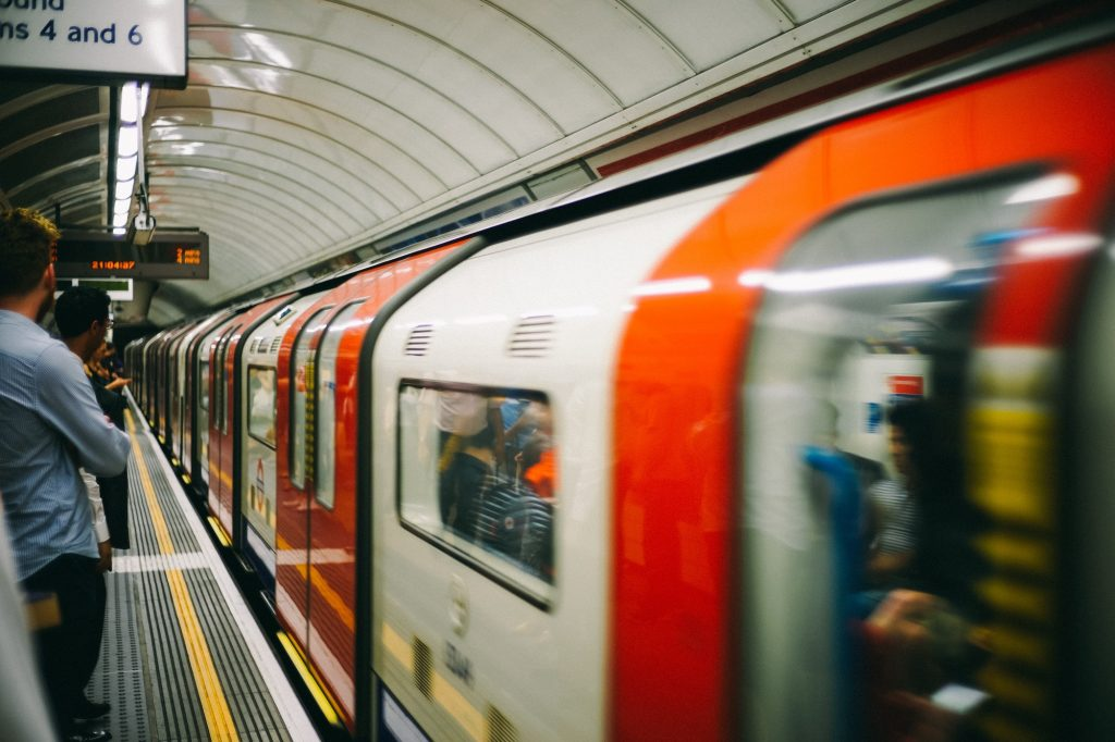 London tube platform with a train pulling up, people wait to get on