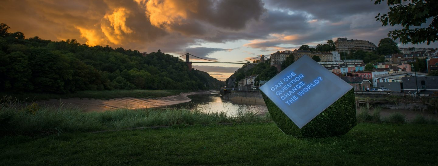 Image shows the We The Curious Curious Cube by the Bristol Basin looking out to the Clifton Suspension Bridge at a cloudy dusk